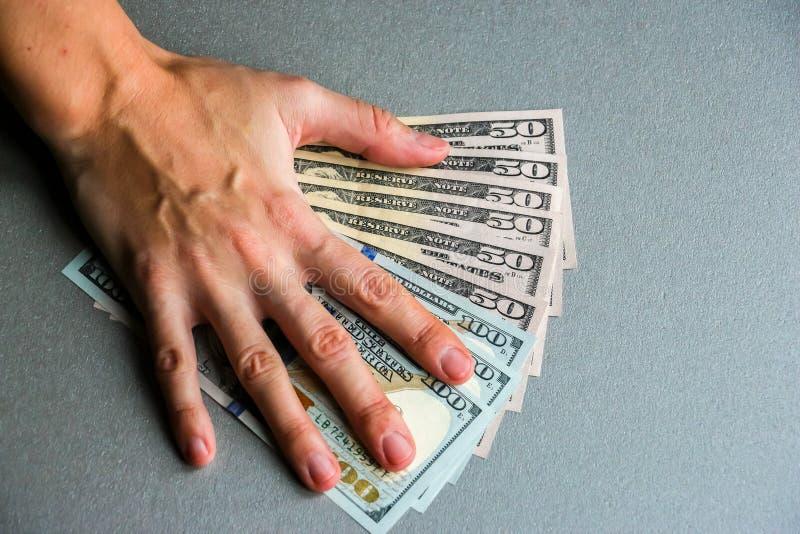 Entregue cientos y cincuenta billetes de banco del dólar fotos de archivo libres de regalías