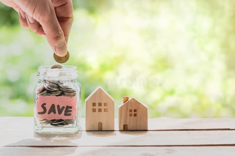 Entregue a colocação da moeda no frasco de vidro da moeda para o dinheiro de salvamento para a casa de compra fotos de stock