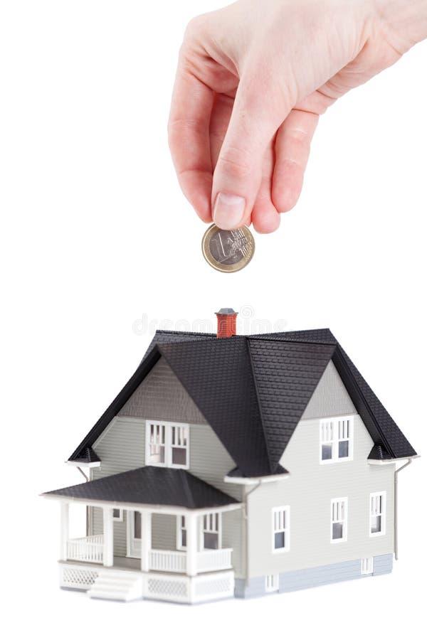Entregue a colocação da moeda no modelo arquitectónico da casa foto de stock