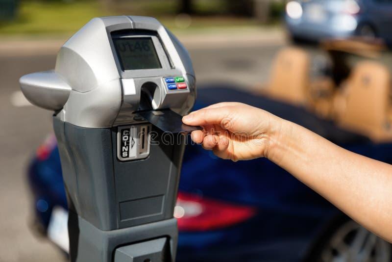 Entregue a colocação do cartão de crédito no medidor de estacionamento com carro convertível fotografia de stock