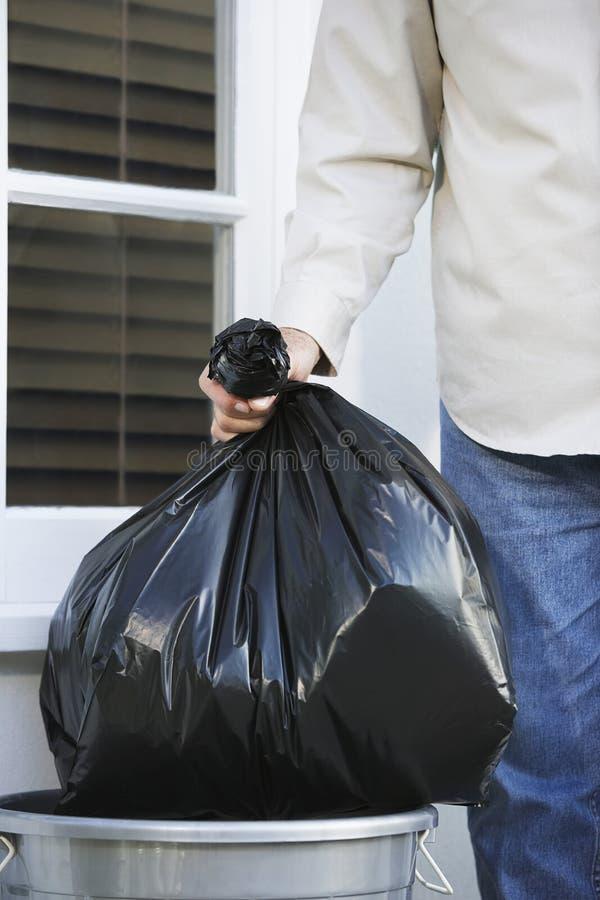 Entregue a colocação do saco de lixo no balde do lixo fotografia de stock