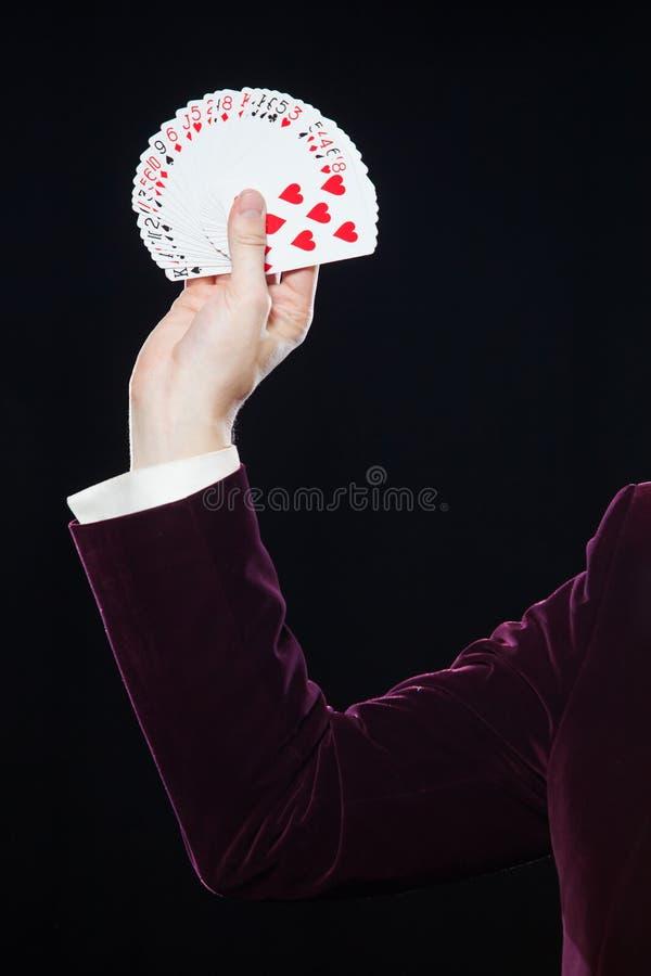 Entregue com close-up dos cartões A seção mestra da exibição do mágico ventilou para fora cartões contra o fundo preto Mágico, Ju imagens de stock
