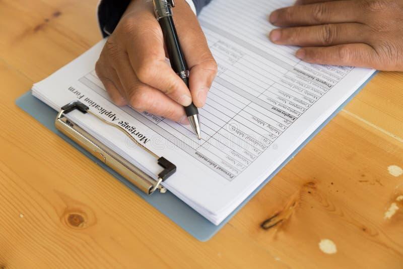 entregue completam a aplicação de empréstimo hipotecário em uma prancheta Um formulário t imagens de stock royalty free