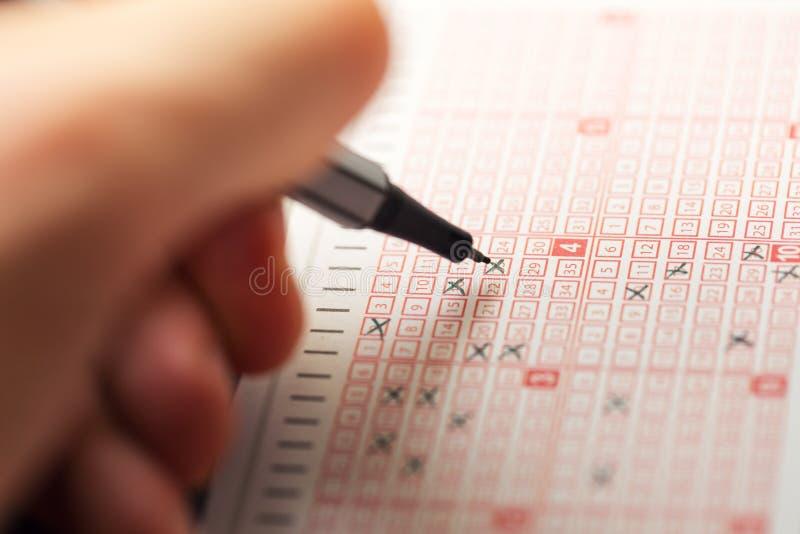 Entregue completar um bilhete de loteria do loto do bingo foto de stock
