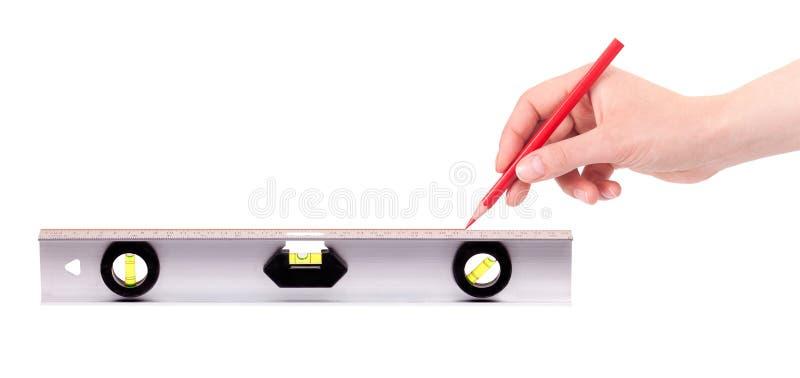 Entregue a desenho a linha vermelha usando um nível de espírito imagens de stock