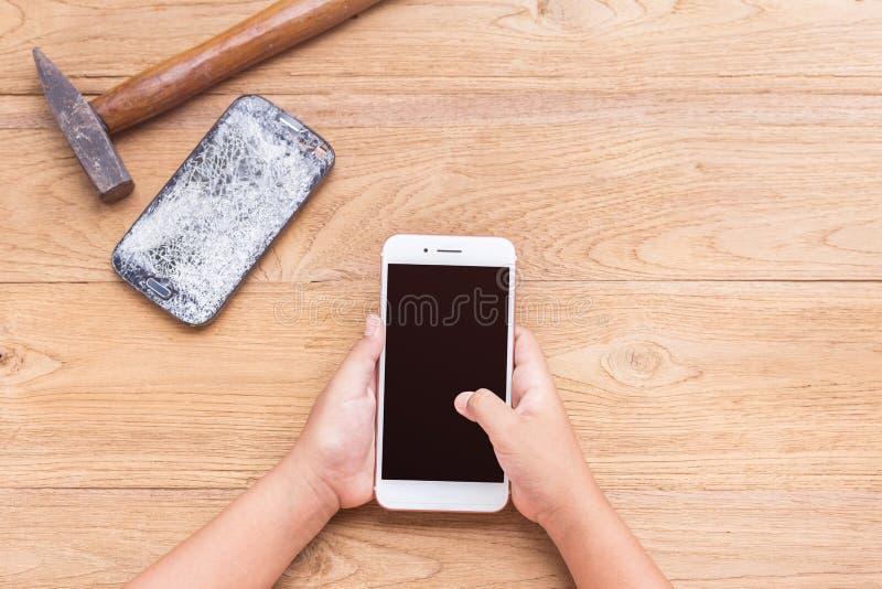 Entregue a escolha do smartphone novo e quebre o velho pelo martelo na madeira imagem de stock royalty free