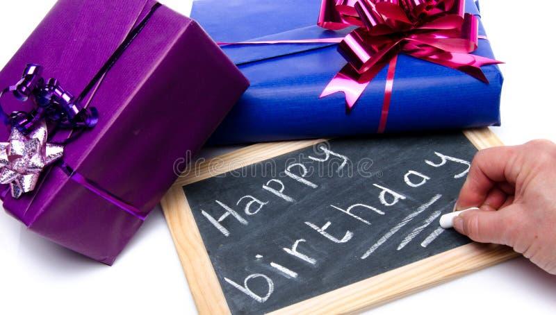 Entregue a escrita do feliz aniversario em um quadro-negro da ardósia com presentes fotos de stock royalty free