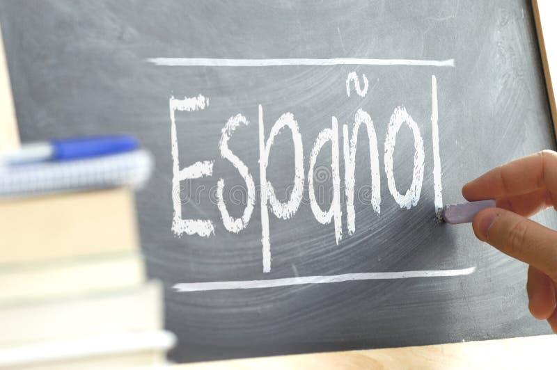 Entregue a escrita em um quadro-negro em uma classe de língua com a palavra & o x22; Spanish& x22; escrito nele fotos de stock royalty free