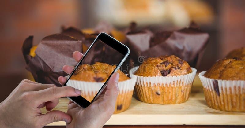 Entregue a fotografia de queques através do telefone esperto na padaria imagem de stock