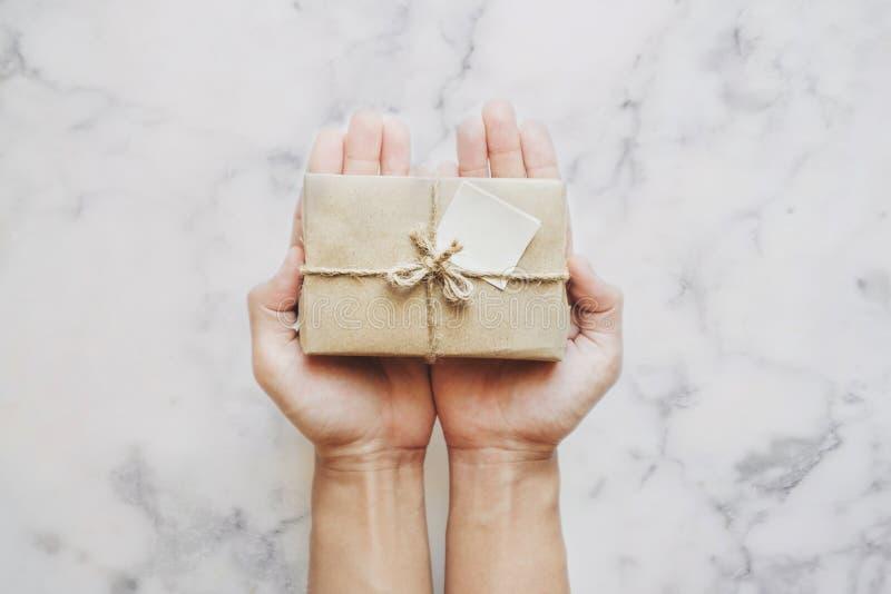 Entregue guardar a caixa de presente do pacote, no fundo de pedra de mármore branco da tabela fotografia de stock