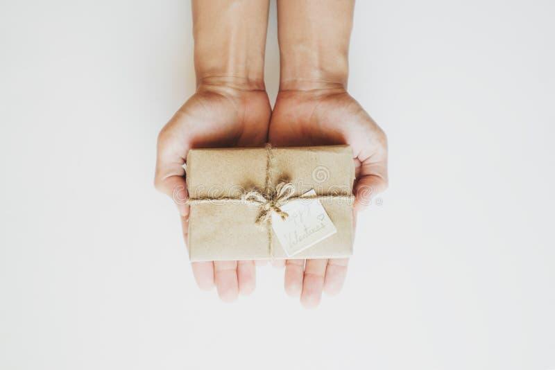 Entregue guardar a caixa de presente marrom com nota feliz dos Valentim, no fundo branco imagem de stock royalty free