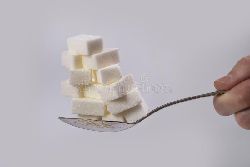 Entregue guardar a colher com a pilha de cubos do açúcar empilhou a nutrição insalubre, fazem dieta e adoçam o conceito do apego imagem de stock