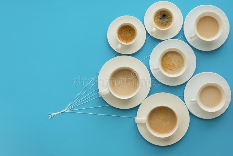 Entregue guardar copos de café com leite e sem na forma dos balões no fundo do papel azul Conceito do tempo ou do bom dia fotografia de stock royalty free