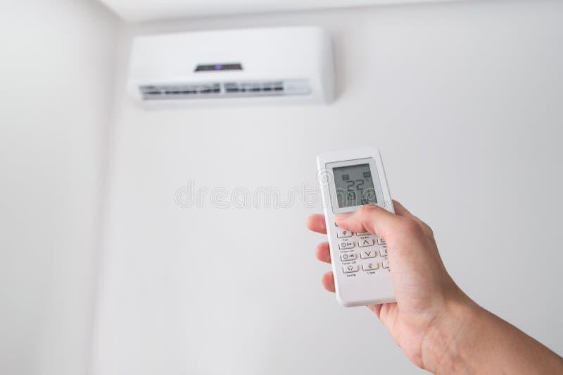 Entregue guardar de controle remoto para o condicionador de ar na parede branca fotos de stock
