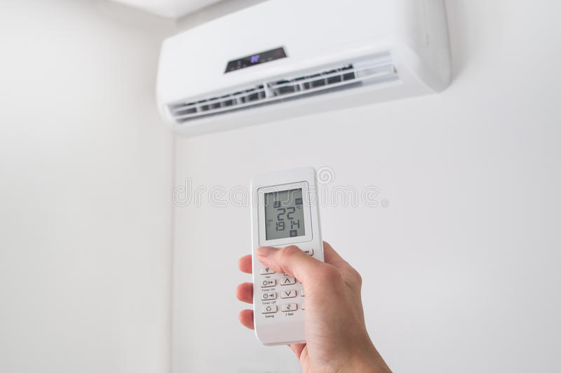 Entregue guardar de controle remoto para o condicionador de ar na parede branca imagens de stock