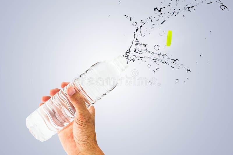 Entregue guardar a garrafa de água potável com respingo no fundo do azul do inclinação foto de stock royalty free