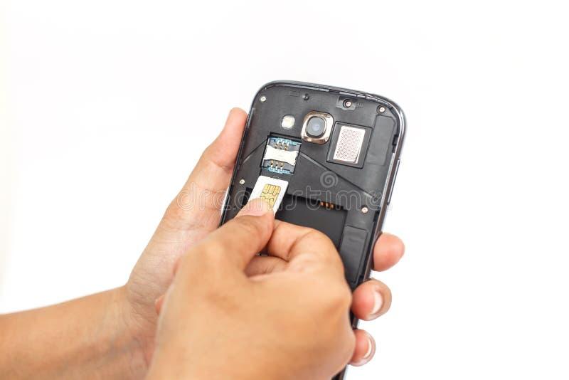 Entregue guardar o cartão do sim e põe-no no smartphone isolado sobre o branco fotos de stock