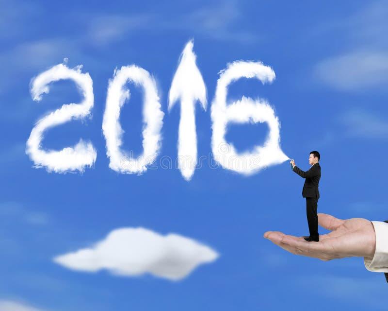 Entregue guardar o homem de negócios que pulveriza a seta 2016 acima das nuvens com o céu foto de stock royalty free