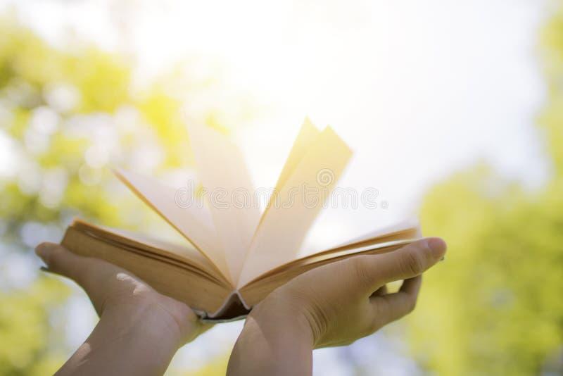 Entregue guardar o livro no céu, no conhecimento e no conceito da sabedoria foto de stock
