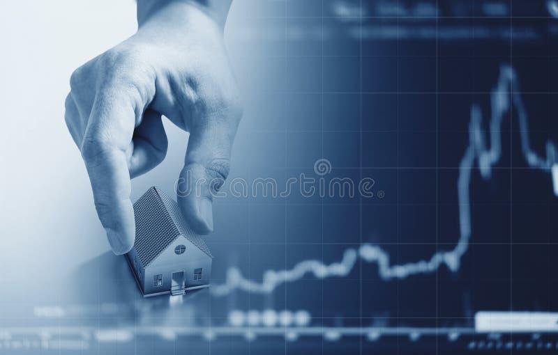 Entregue guardar o modelo da casa, com levantar o fundo do gráfico Negócio e investimento dos bens imobiliários no conceito dos b fotografia de stock royalty free