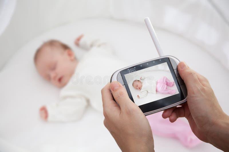 Entregue guardar o monitor video do bebê para a segurança do bebê imagem de stock