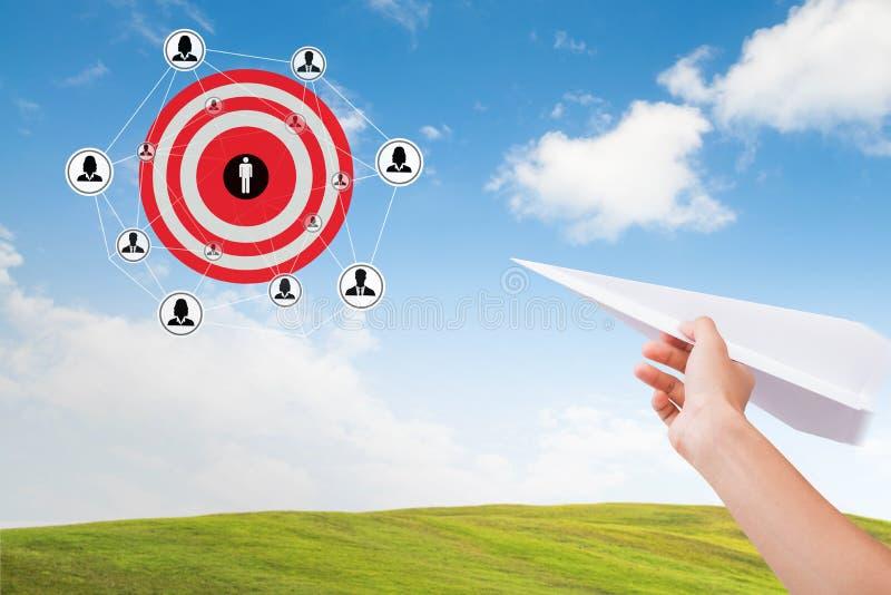 Entregue guardar o plano de papel com o alvo dos objetivos do mercado no céu imagens de stock
