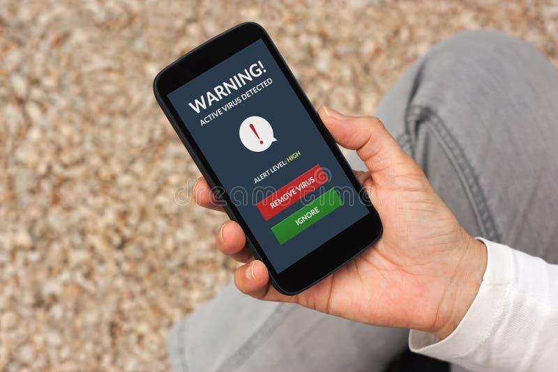 Entregue guardar o smartphone com alerta do vírus na tela imagem de stock royalty free