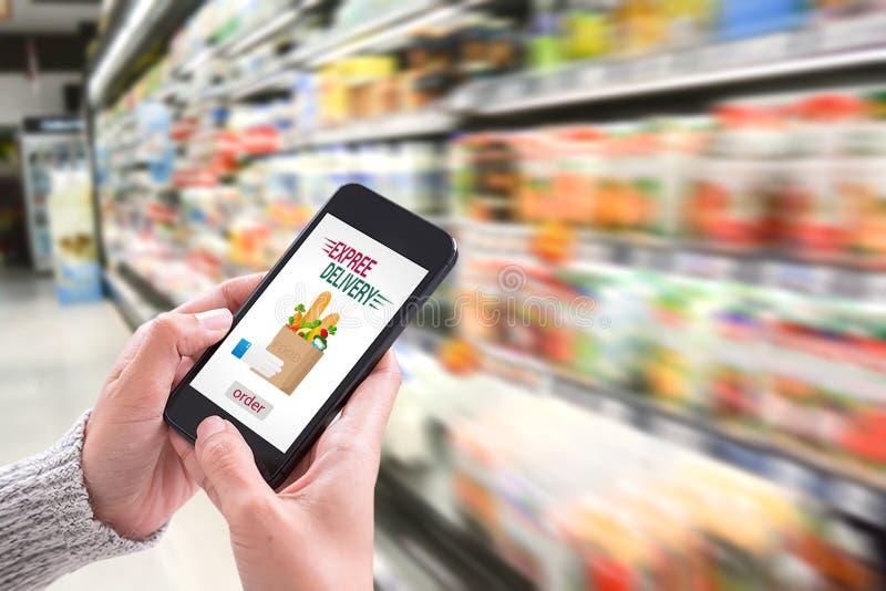 Entregue guardar o smartphone com serviço de entrega app na tela imagens de stock