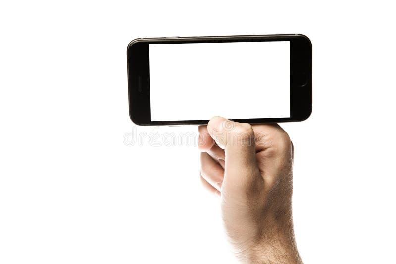 Entregue guardar o smartphone, tela vazia no fundo branco fotos de stock