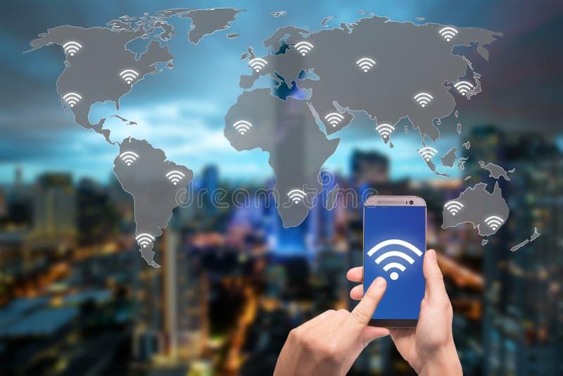 Entregue guardar o telefone celular com ícone do wifi no conceito da conexão do mapa do mundo e da cidade e de rede fotografia de stock royalty free