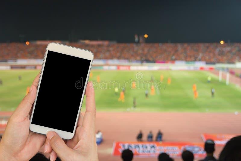 Entregue guardar o telefone esperto móvel com tela preta, socce borrado fotos de stock