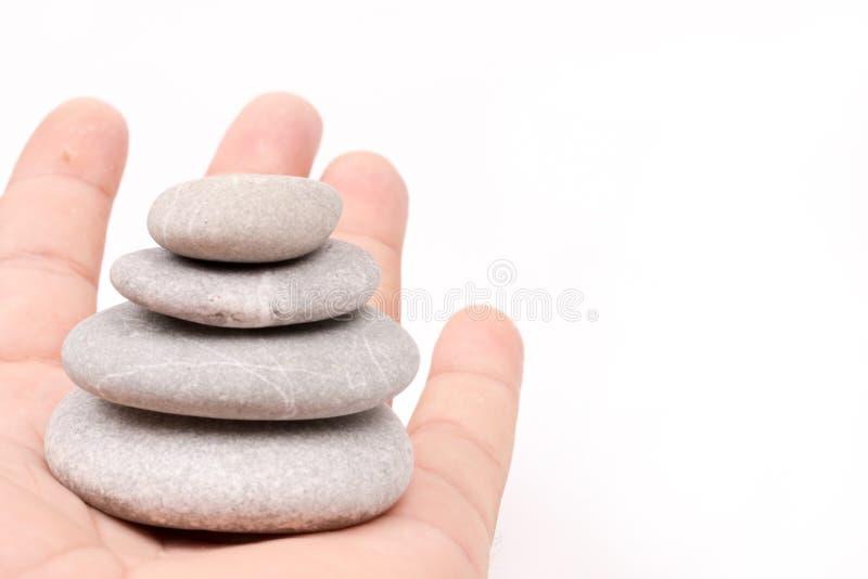 Entregue guardar pedras cinzentas equilibradas sobre o fundo branco imagens de stock royalty free