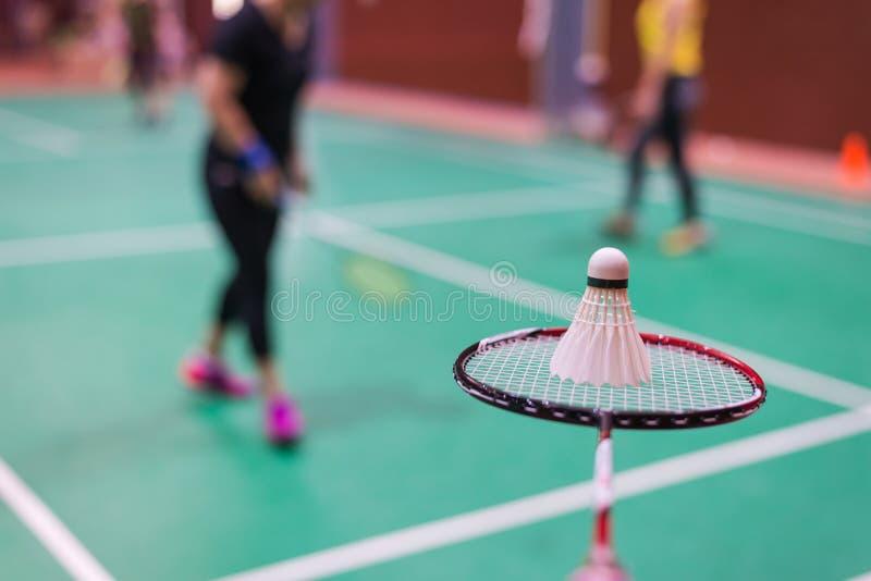entregue guardar a raquete e a peteca de badminton na corte de badminton foto de stock royalty free