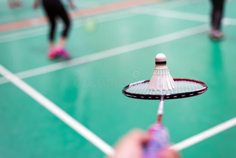 entregue guardar a raquete e a peteca de badminton na corte de badminton fotografia de stock royalty free