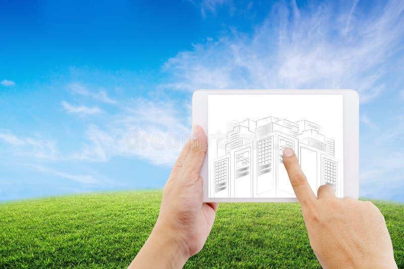 entregue guardar a tabuleta do homem de negócios com esboços do desenho do projeto de construção no fundo da natureza imagens de stock royalty free