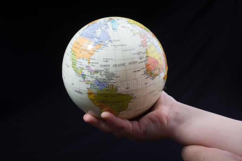 Entregue guardar um globo com o mapa nele imagens de stock