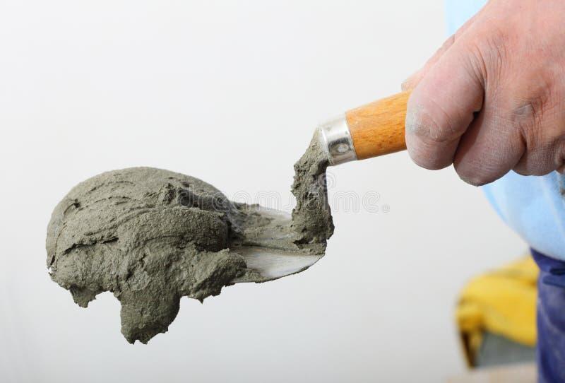 Entregue guardar uma pá de pedreiro da cubeta com almofariz do cimento fotografia de stock
