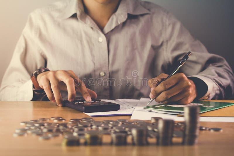 Entregue guardar uma pena e uma calculadora na tabela com uma medalha que reconhece o fundo claro do negócio da computação e do p imagem de stock royalty free