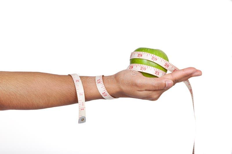 Entregue guardarar a maçã verde com fita de medição. fotos de stock
