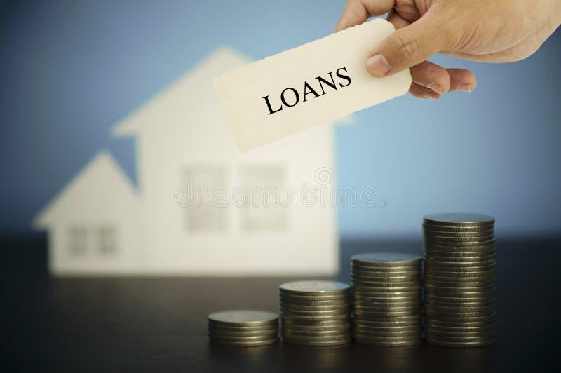 Entregue hokding e mostre o sinal dos empréstimos na pilha de moedas e casa do dinheiro, conceito na compra, venda e finança da c fotografia de stock