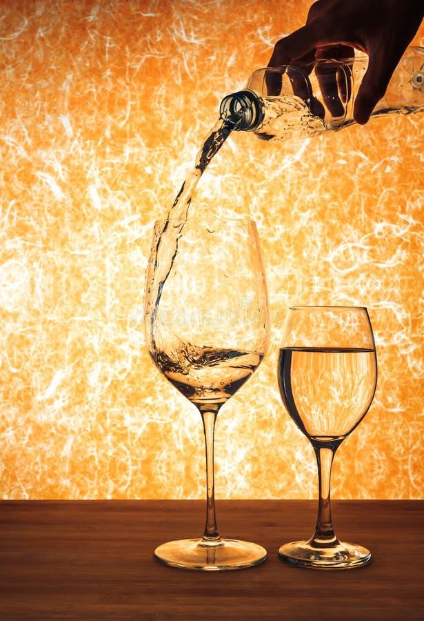 Entregue la botella del agujero y el agua de colada a la copa de vino imagen de archivo libre de regalías
