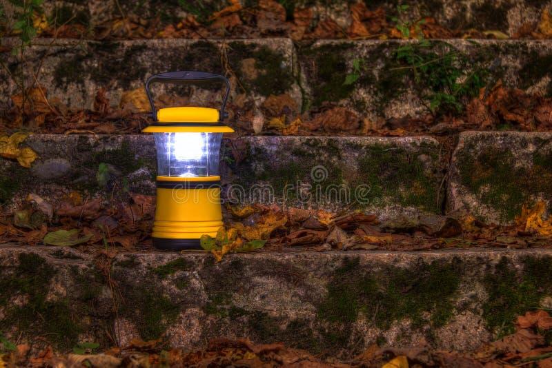 Entregue a lanterna nas escadas cobertas com as folhas secas fotos de stock