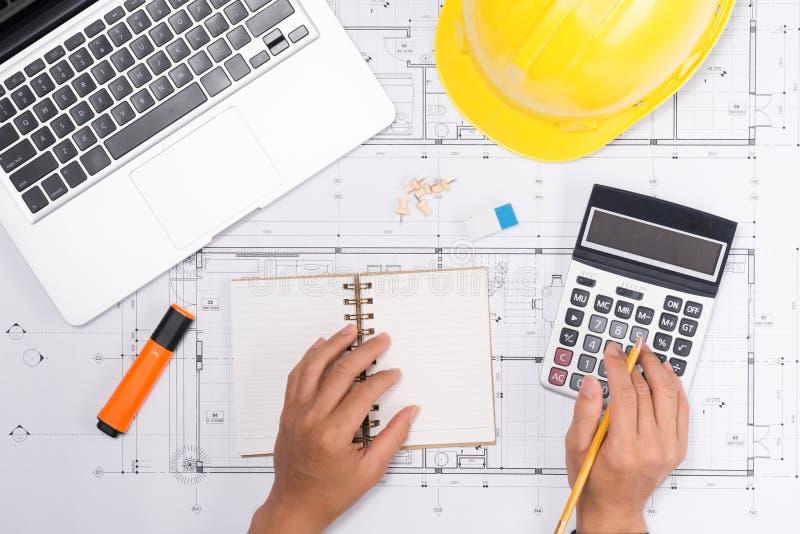 Entregue los planes de la construcci?n con las herramientas amarillas del casco y de dibujo en modelos imágenes de archivo libres de regalías