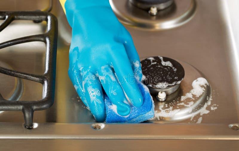 Entregue a luva de borracha vestindo ao limpar o fogão escala superior com o s imagem de stock