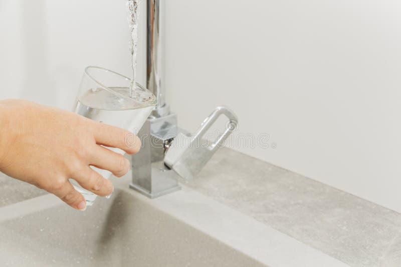Entregue manter um vidro da água derramado do torneira da cozinha imagem de stock