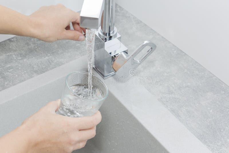 Entregue manter um vidro da água derramado do torneira da cozinha imagens de stock