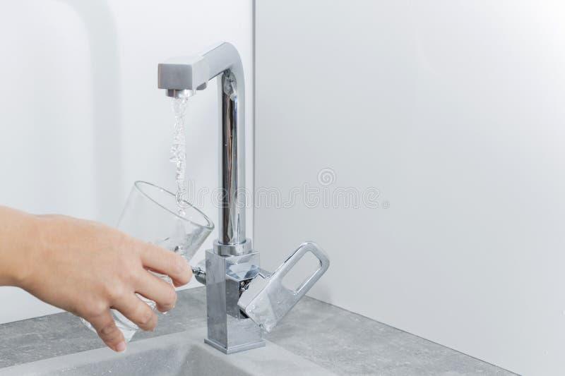 Entregue manter um vidro da água derramado do torneira da cozinha foto de stock