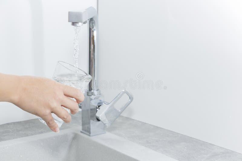 Entregue manter um vidro da água derramado do torneira da cozinha imagem de stock royalty free