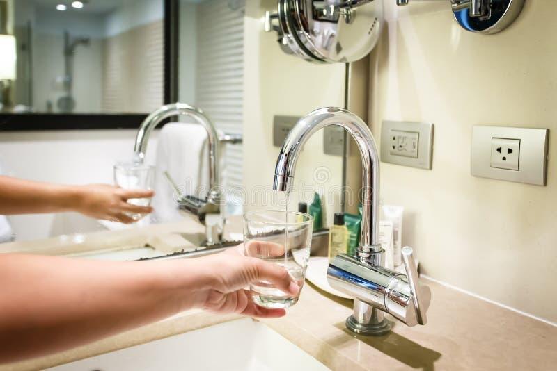 Entregue manter um vidro da água derramado do torneira do banheiro foto de stock royalty free