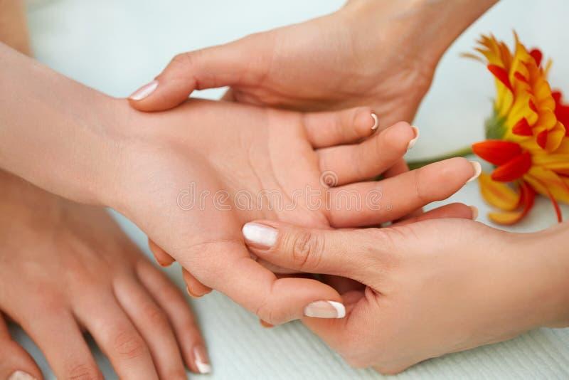 Entregue a massagem O louro bonito obtém o tratamento dos termas no salão de beleza imagens de stock royalty free